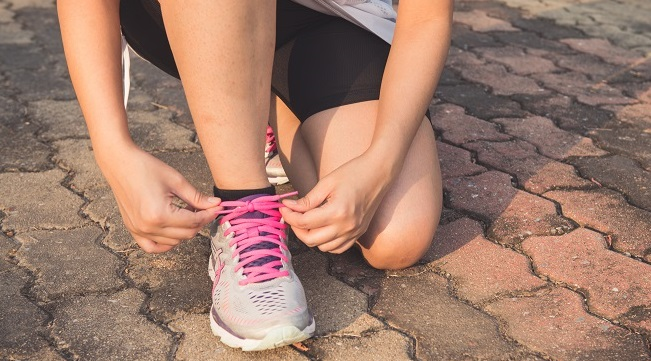 Running shoes - woman tying shoe laces. Closeup of female sport