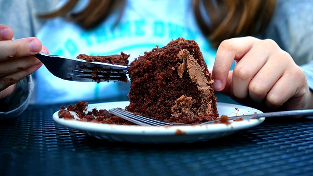 Girl eating cake with knife and fork