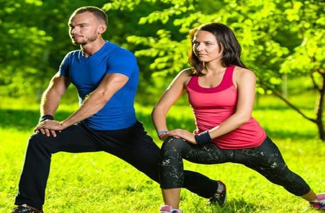 Man and woman in park stretching their hip flexors.