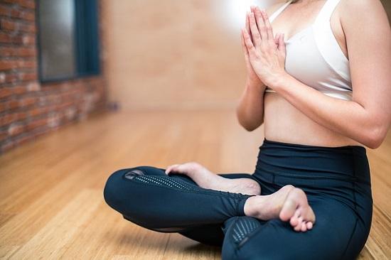 Woman doing yoga on wooden floor.