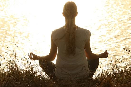 Woman meditating by a lake at sunrise.