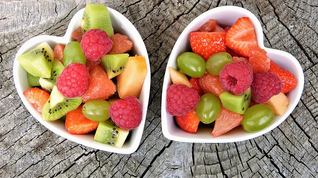 Two heart-shaped bowls of fruit on a wood surface.