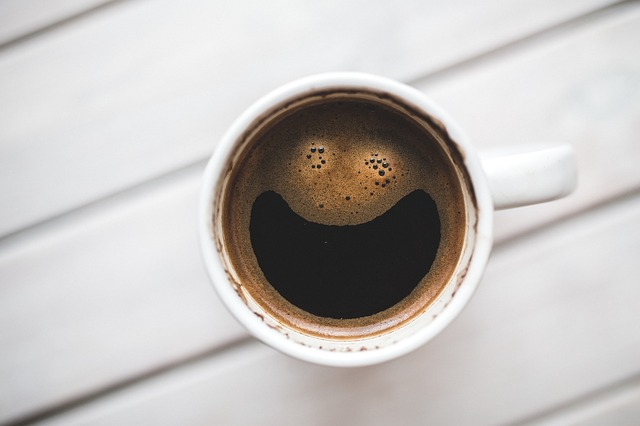 Cup of coffee with a smiley face on a table.