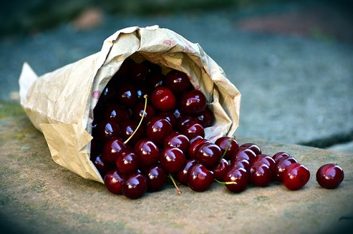 cherries in a paper bag on a stone surface.