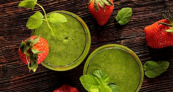 Green smoothies on a table with strawberries.