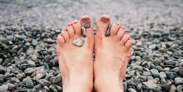 Woman's feet on pebble beach.