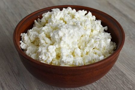 Bowl with cottage cheese on a wooden table.