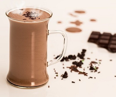 Glass of chocolate milk with dark chocolate next to it.