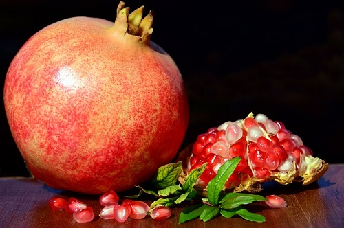 Pomegranate with seeds on a table.