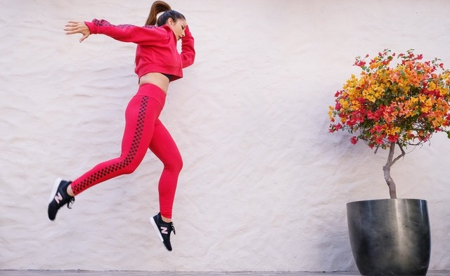 Woman in a red tracksuit jumping near a wall.