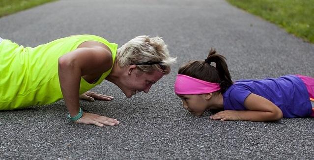 woman and girl doing push-ups