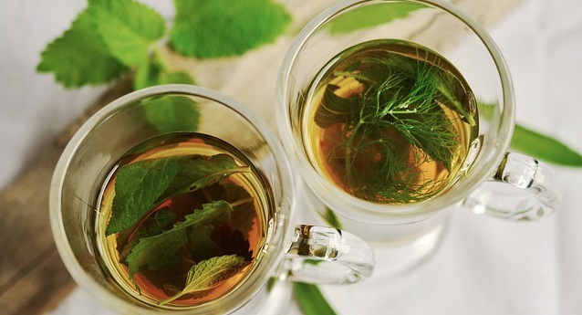 cups of herbal tea on table with leaves