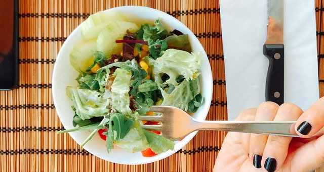 Bowl of salad on a table with a hand holding a fork above it.