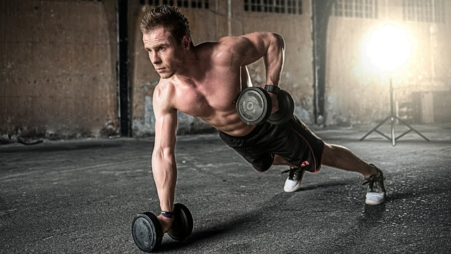 Man training with dumbbells in gym.