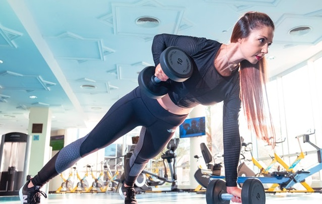 Woman training with weights in the gym.