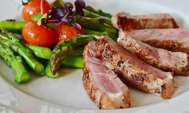 Asparagus, meat and tomatoes on a plate.